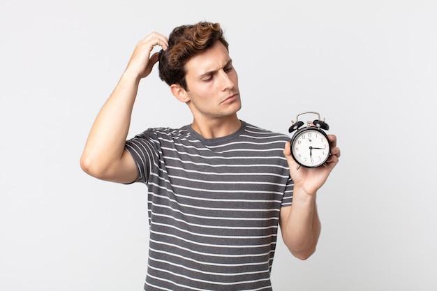 Młody przystojny mężczyzna czuje się zakłopotany i zdezorientowany, drapiąc się po głowie i trzymający budzik
