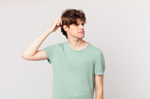 Młody przystojny mężczyzna czuje się zakłopotany i zdezorientowany, drapiąc się po głowie