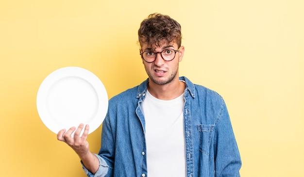 Młody przystojny mężczyzna czuje się zakłopotany i zdezorientowany. koncepcja pustego naczynia