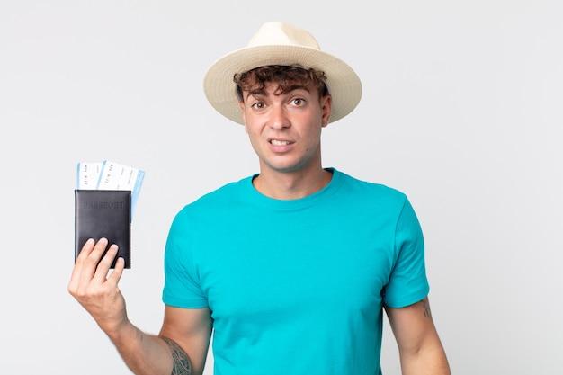 Młody przystojny mężczyzna czuje się zakłopotany i zdezorientowany. podróżnik trzymający paszport