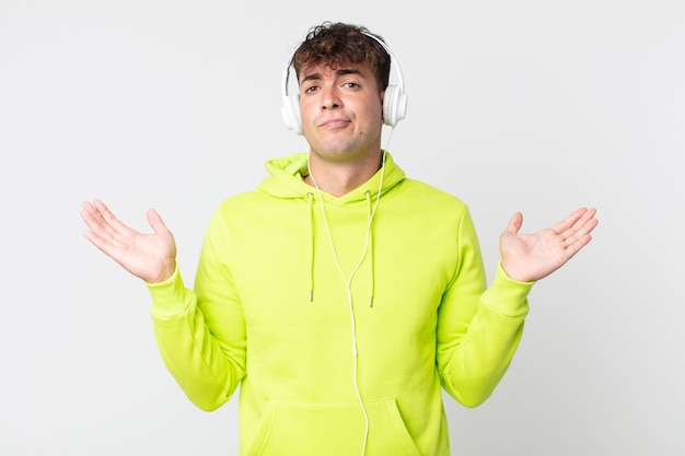 Młody przystojny mężczyzna czuje się zakłopotany i zdezorientowany, wątpi i słucha słuchawek