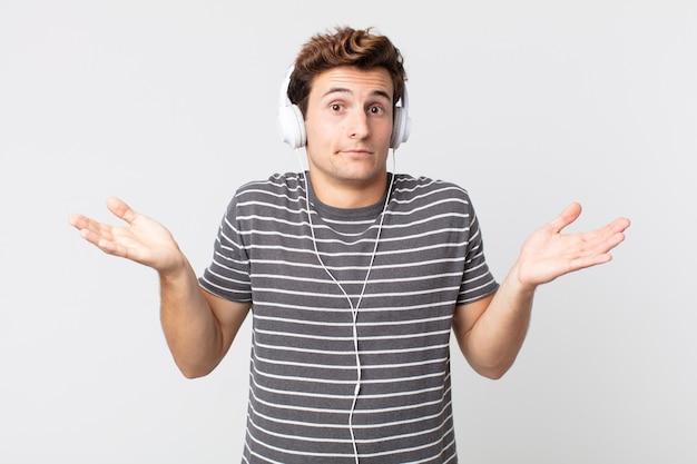 Młody przystojny mężczyzna czuje się zakłopotany, zdezorientowany i wątpi. koncepcja muzyki do słuchania