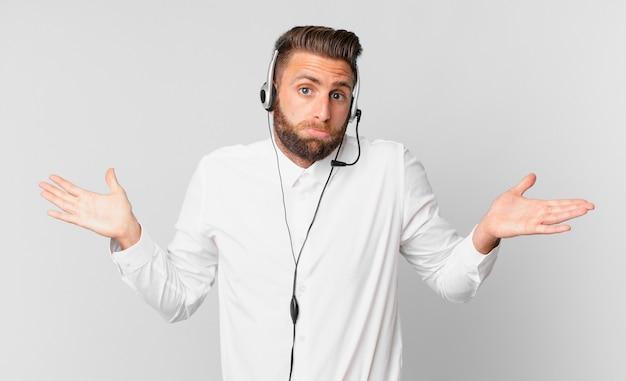 Młody przystojny mężczyzna czuje się zakłopotany, zdezorientowany i wątpi. koncepcja telemarketingu