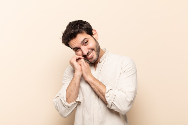 Młody przystojny mężczyzna czuje się zakochany i wygląda słodko, uroczo i szczęśliwie, romantycznie uśmiecha się z rękami obok twarzy