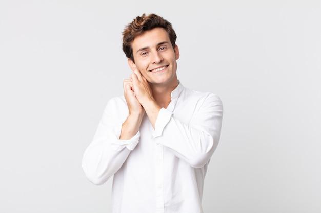 Młody przystojny mężczyzna czuje się zakochany i wygląda słodko, uroczo i szczęśliwie, uśmiechając się romantycznie z rękami przy twarzy