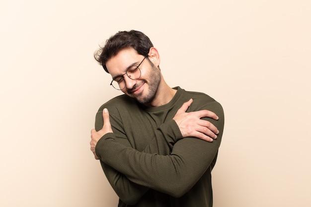 Młody przystojny mężczyzna czuje się zakochany, uśmiecha się, przytula i przytula siebie, pozostaje samotny, jest samolubny i egocentryczny