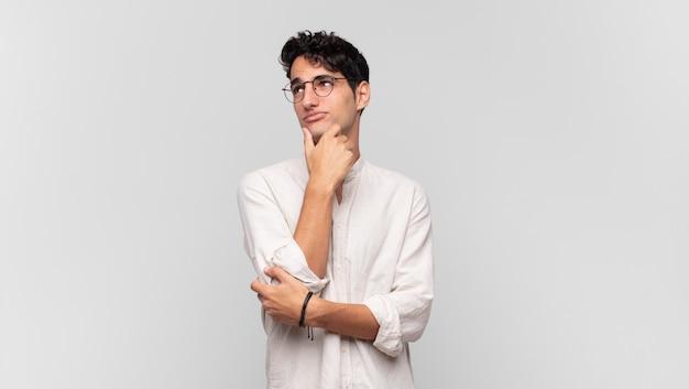 Młody przystojny mężczyzna czuje się zamyślony, zastanawia się lub ma pomysły