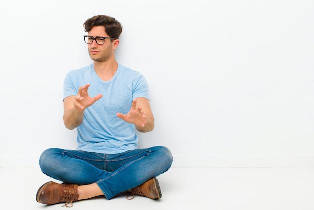 Młody przystojny mężczyzna czuje się zdegustowany i mdłości, odsuwa się od czegoś paskudnego, śmierdzącego lub śmierdzącego, mówiąc: fuj, siedząc na podłodze