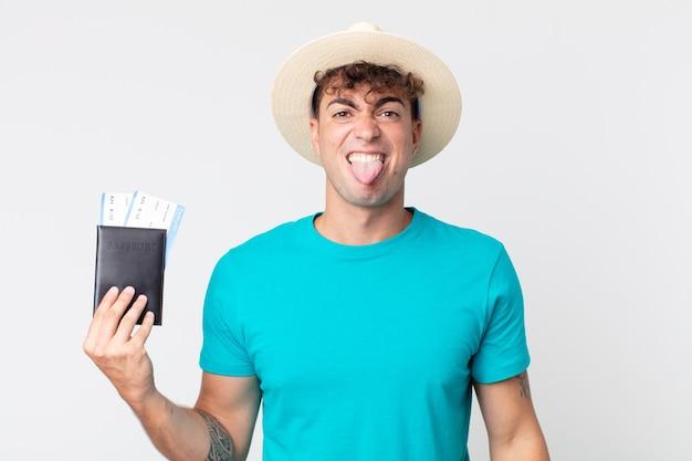 Młody przystojny mężczyzna czuje się zdegustowany i podrażniony i wymawia język. podróżnik trzymający paszport
