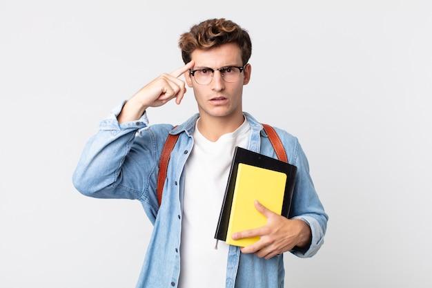 Młody przystojny mężczyzna czuje się zdezorientowany i zdezorientowany, pokazując, że jesteś szalony. koncepcja studenta uniwersytetu