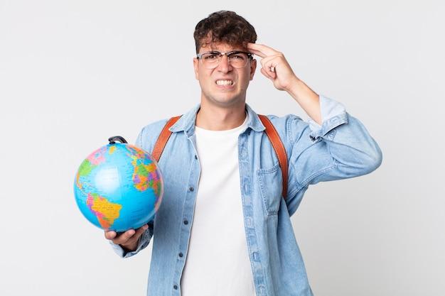 Młody przystojny mężczyzna czuje się zdezorientowany i zdezorientowany, pokazując, że jesteś szalony. student trzymający mapę kuli ziemskiej