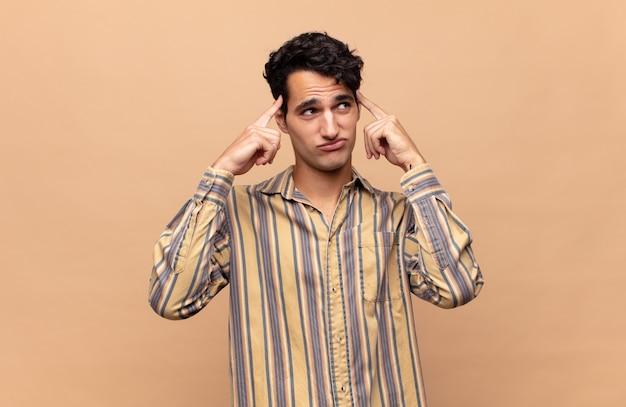 Młody przystojny mężczyzna czuje się zdezorientowany lub wątpi, koncentruje się na pomyśle, intensywnie myśli, chce skopiować miejsce z boku