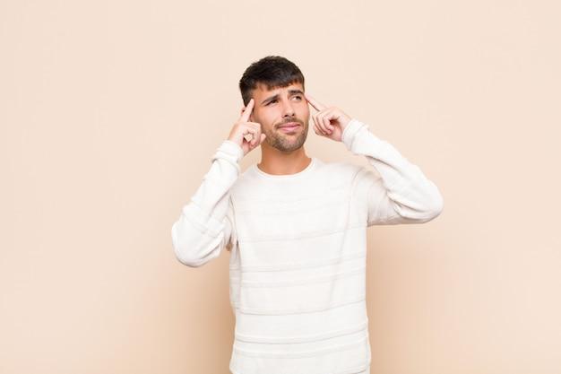 Młody przystojny mężczyzna czuje się zdezorientowany lub wątpiąc, koncentrując się na pomyśle, ciężko myśląc, szukając miejsca na ciepłą ścianę
