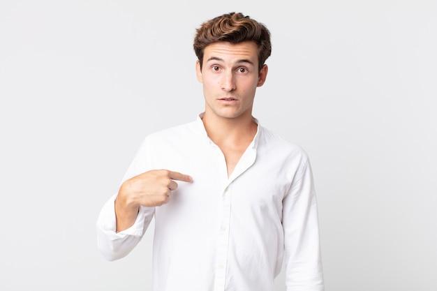 Młody, przystojny mężczyzna czuje się zdezorientowany, zdezorientowany i niepewny, wskazując na siebie, zastanawiając się i pytając, kto, ja?