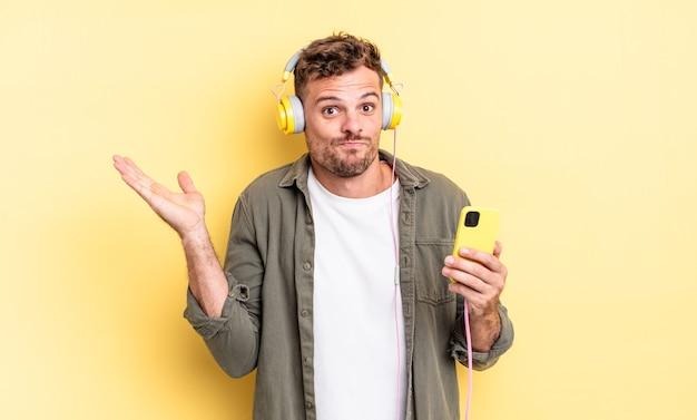 Młody przystojny mężczyzna czuje się zdziwiony, zdezorientowany i wątpi w koncepcję słuchawek i smartfona