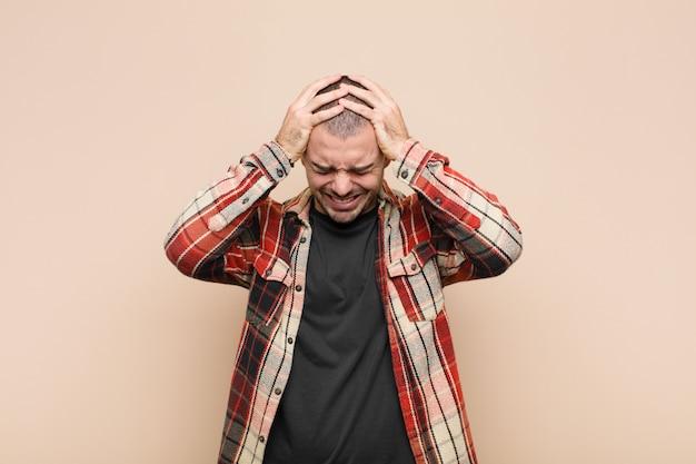 Młody przystojny mężczyzna czuje się zestresowany i sfrustrowany, podnosząc ręce do głowy, czując się zmęczony, nieszczęśliwy i z migreną na ścianie