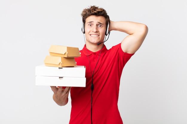 Młody przystojny mężczyzna czuje się zestresowany, niespokojny lub przestraszony, z rękami na głowie. koncepcja fast foodów na wynos