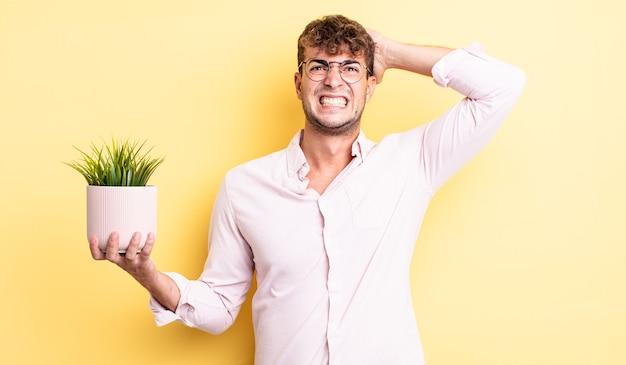 Młody przystojny mężczyzna czuje się zestresowany, niespokojny lub przestraszony, z rękami na głowie. koncepcja roślin ozdobnych
