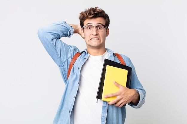 Młody przystojny mężczyzna czuje się zestresowany, niespokojny lub przestraszony, z rękami na głowie. koncepcja studenta uniwersytetu