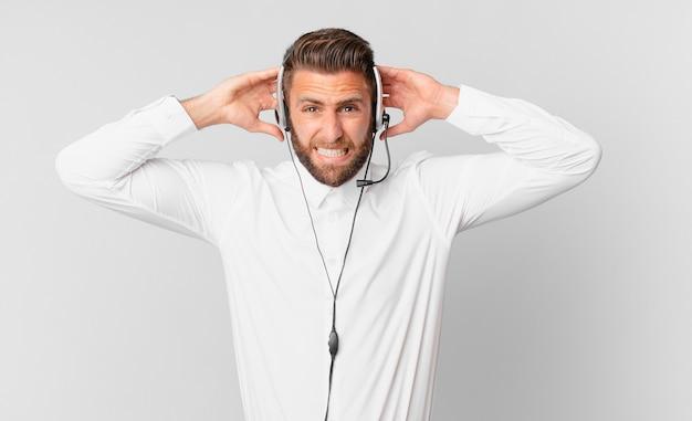 Młody przystojny mężczyzna czuje się zestresowany, niespokojny lub przestraszony, z rękami na głowie. koncepcja telemarketingu