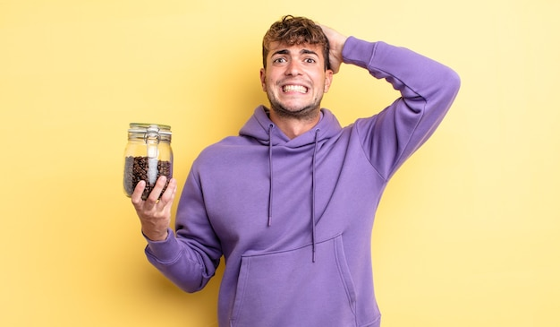 Młody przystojny mężczyzna czuje się zestresowany, niespokojny lub przestraszony, z rękami na głowie. koncepcja ziaren kawy