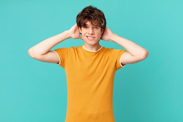 Młody przystojny mężczyzna czuje się zestresowany, niespokojny lub przestraszony, z rękami na głowie