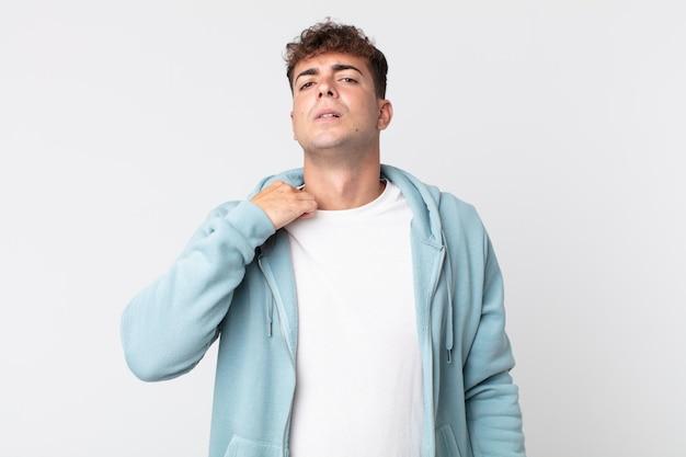 Młody przystojny mężczyzna czuje się zestresowany, niespokojny, zmęczony i sfrustrowany, ciągnie za koszulkę, wygląda na sfrustrowanego problemem