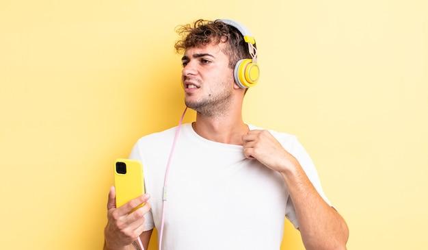 Młody przystojny mężczyzna czuje się zestresowany, niespokojny, zmęczony i sfrustrowany. koncepcja słuchawek i smartfona