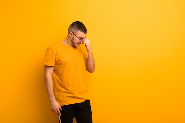 Młody przystojny mężczyzna czuje się zestresowany, nieszczęśliwy i sfrustrowany, dotyka czoła i cierpi na migrenę silnego bólu głowy na płaskiej ścianie