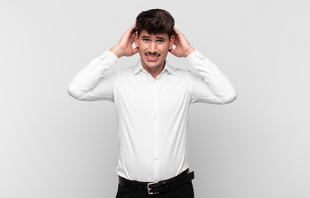 Młody przystojny mężczyzna czuje się zestresowany, zmartwiony, niespokojny lub przestraszony, z rękami na głowie, panikuje podczas pomyłki