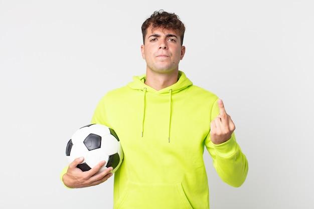 Młody przystojny mężczyzna czuje się zły, zirytowany, buntowniczy i agresywny i trzyma piłkę nożną