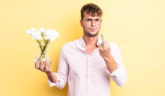 Młody przystojny mężczyzna czuje się zły, zirytowany, buntowniczy i agresywny. koncepcja kwiaty