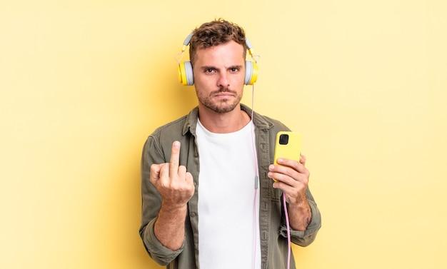 Młody przystojny mężczyzna czuje się zły, zirytowany, buntowniczy i agresywny koncepcja słuchawek i smartfona