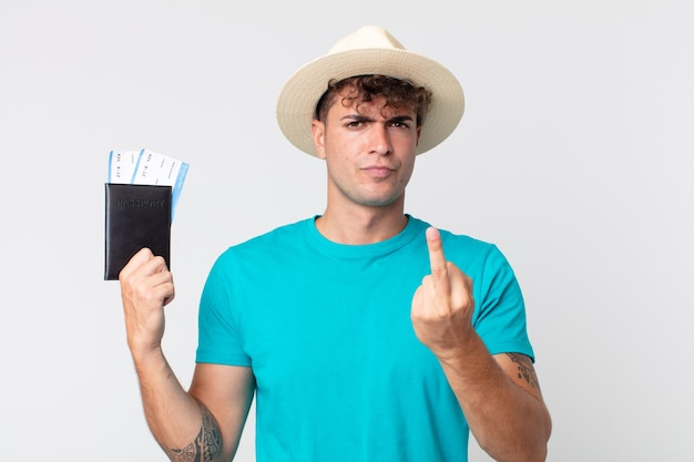 Młody przystojny mężczyzna czuje się zły, zirytowany, buntowniczy i agresywny. podróżnik trzymający paszport