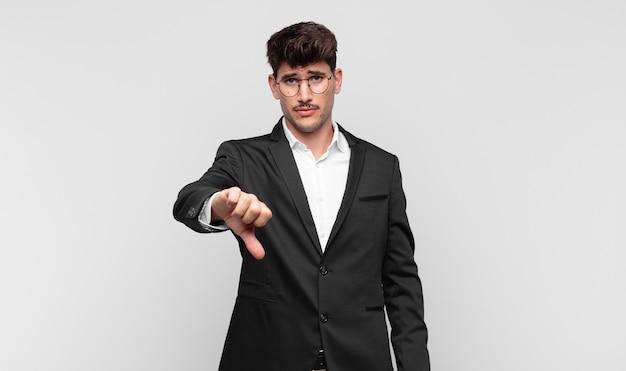 Młody przystojny mężczyzna czuje się zły, zły, zirytowany, rozczarowany lub niezadowolony, pokazując kciuki w dół z poważnym spojrzeniem