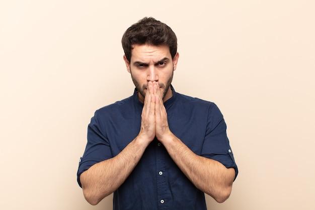 Młody przystojny mężczyzna czuje się zmartwiony, pełen nadziei i religijny, modli się wiernie z przyciśniętymi dłońmi, błagając o przebaczenie