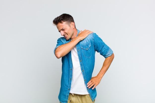 Młody przystojny mężczyzna czuje się zmęczony, zestresowany, niespokojny, sfrustrowany i przygnębiony, cierpi na ból pleców lub szyi