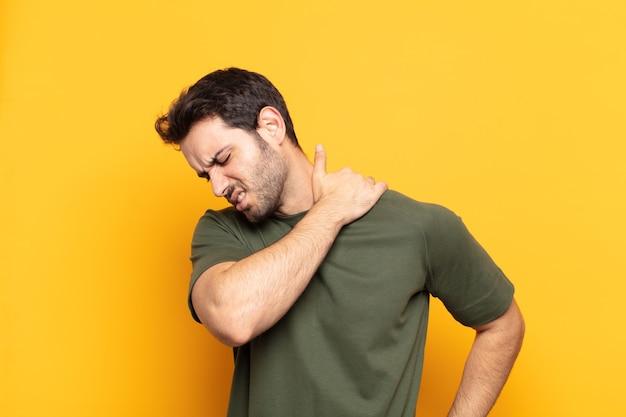 Młody przystojny mężczyzna czuje się zmęczony, zestresowany, niespokojny, sfrustrowany i przygnębiony, cierpi z powodu bólu pleców lub karku
