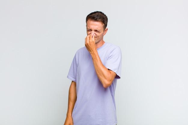 Młody przystojny mężczyzna czuje się zniesmaczony i trzyma nos, żeby nie poczuć nieprzyjemnego zapachu