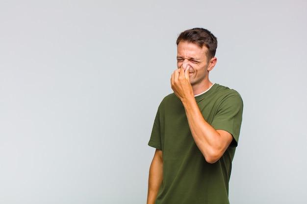 Młody przystojny mężczyzna czuje się zniesmaczony i trzyma nos, żeby nie poczuć obrzydliwego i nieprzyjemnego smrodu