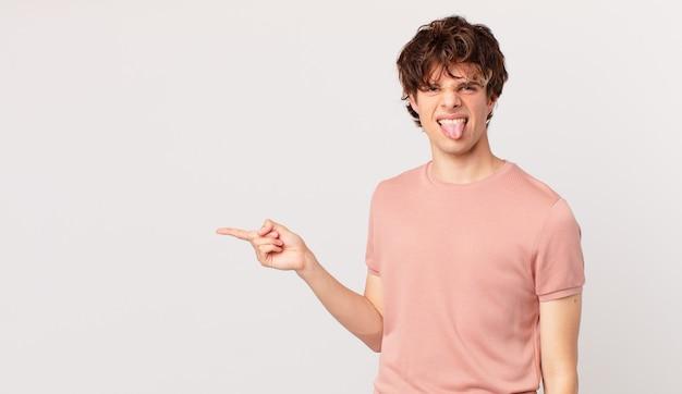 Młody przystojny mężczyzna czuje się zniesmaczony i zirytowany i wymawia język