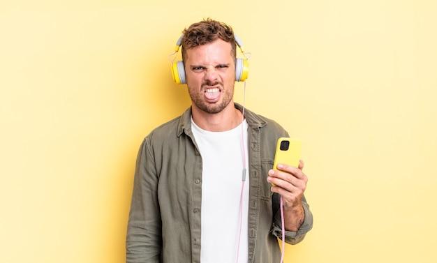 Młody przystojny mężczyzna czuje się zniesmaczony i zirytowany, wyciągając język ze słuchawek i koncepcji smartfona