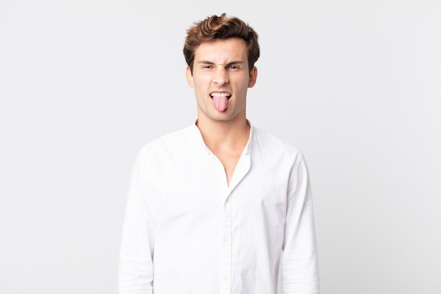 Młody przystojny mężczyzna czuje się zniesmaczony i zirytowany, wystawia język, nie lubi czegoś paskudnego i obrzydliwego