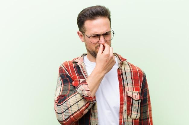 Młody przystojny mężczyzna czuje się zniesmaczony, trzymając nos, aby uniknąć smrodu i nieprzyjemnego smrodu