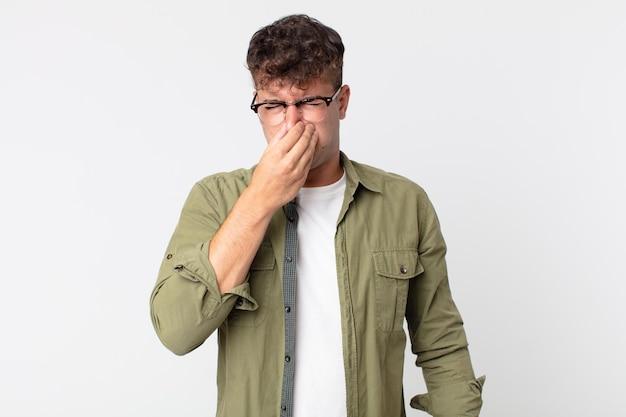 Młody przystojny mężczyzna czuje się zniesmaczony, zatyka nos, aby uniknąć nieprzyjemnego zapachu smrodu