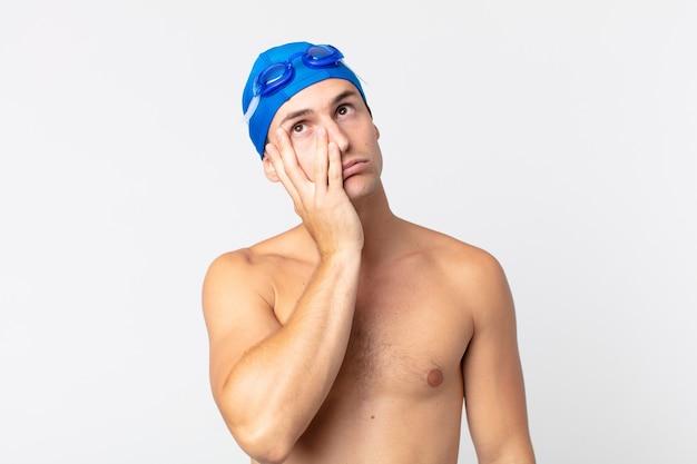 Młody przystojny mężczyzna czuje się znudzony, sfrustrowany i senny po męczącym dniu. koncepcja pływaka