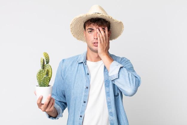 Młody przystojny mężczyzna czuje się znudzony, sfrustrowany i senny po męczącym dniu. rolnik trzymający ozdobnego kaktusa
