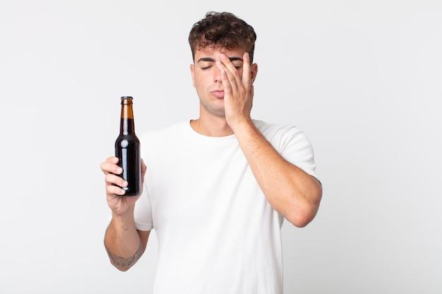 Młody przystojny mężczyzna czuje się znudzony, sfrustrowany i senny po męczącym i trzymającym butelkę piwa