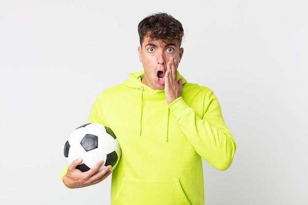 Młody przystojny mężczyzna czuje się zszokowany i przestraszony i trzyma piłkę nożną