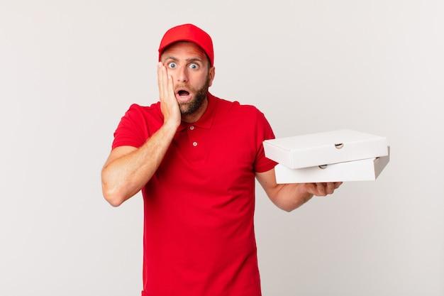 Młody przystojny mężczyzna czuje się zszokowany i przestraszony. koncepcja dostarczania pizzy